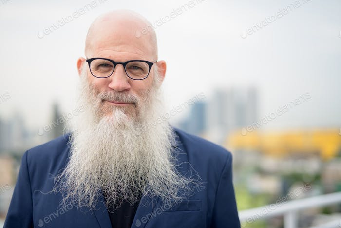 Face of mature handsome bald bearded businessman wearing eyeglasses against view of the city