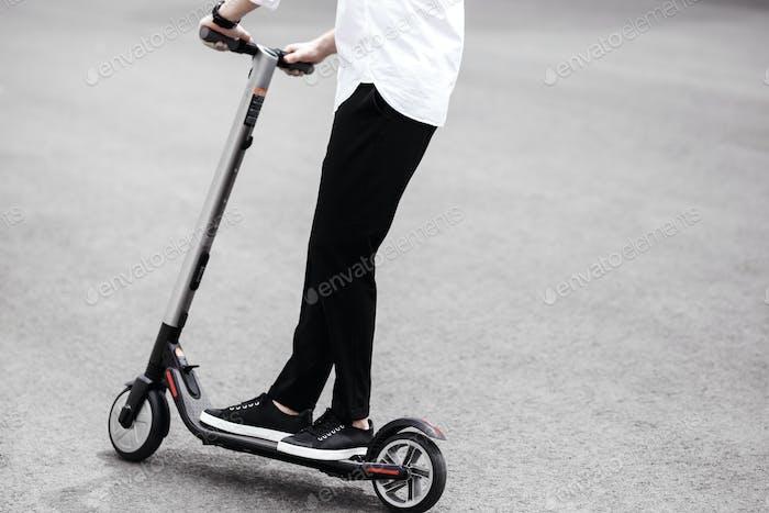 Moderner Mann in stilvollen Schwarz-Weiß-Outfit Reiten elektrische sco