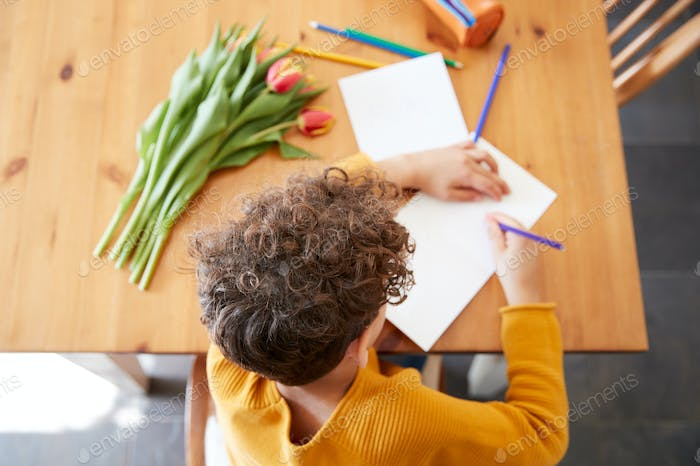 Overhead Shot Of Young Boy At Home With Bunch Of Flowers Writing In Mothers Day Card