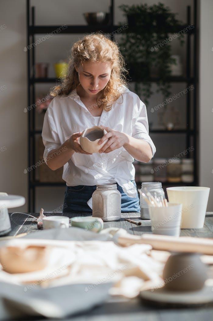 Female potter glazing raw unburned ceramic cup using brush. Earthenware mug putting colorant on