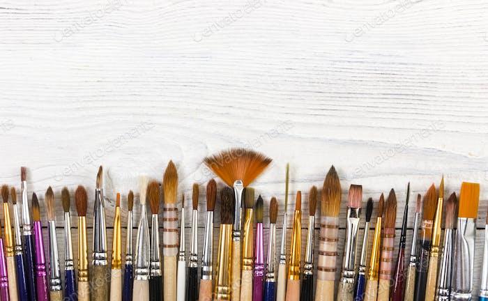 Artistic brushes on light wooden background.