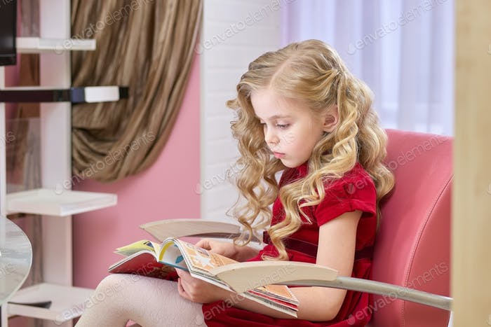 Little girl reading magazine