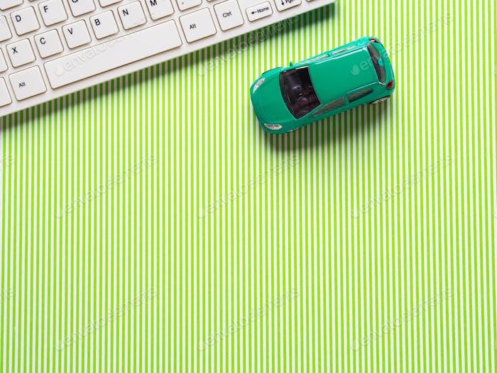Grüner Hintergrund mit Tastatur und Spielzeugauto