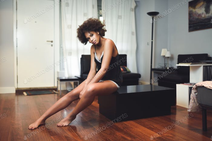 Black topless woman with afro hairstyle sitting in a couch
