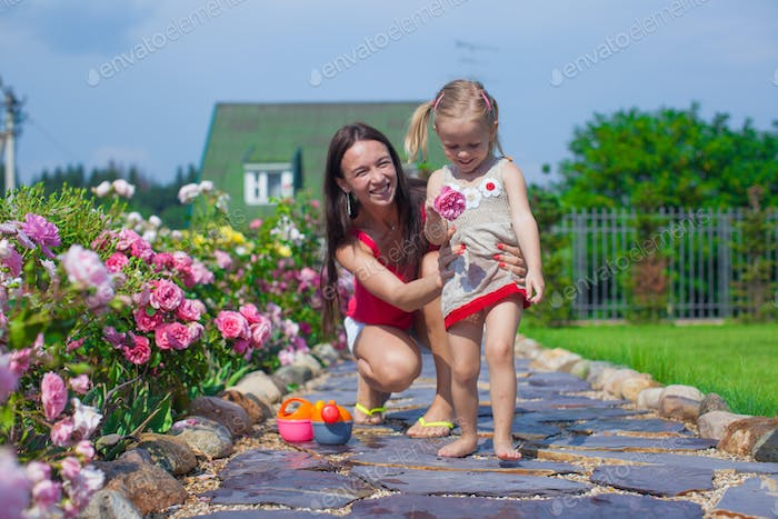 Young mother with her cute daughter have fun in the garden summer time