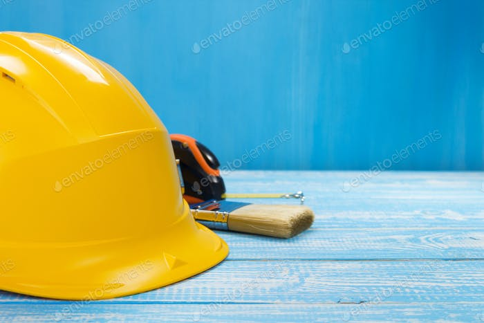 construction helmet and tools on wooden table