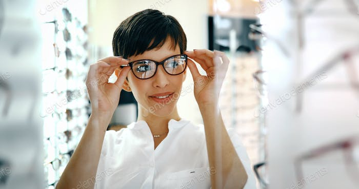health care, eyesight and vision concept - happy woman choosing glasses at optics store