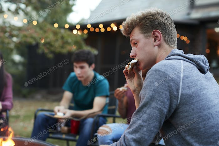 Teenage boy eating somore with friends at a fire pit