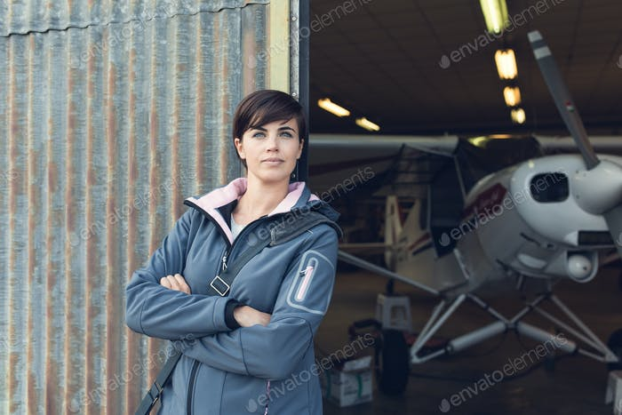 Smiling woman leaning against the hangar walls