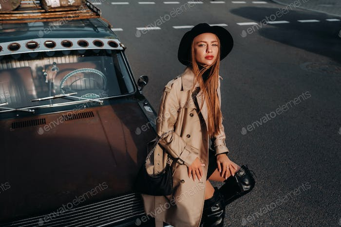 A stylish young woman in a beige coat and black hat on a city street sits on the hood of a car at