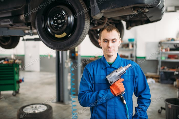 Technician with pneumatic wrench, car on the lift