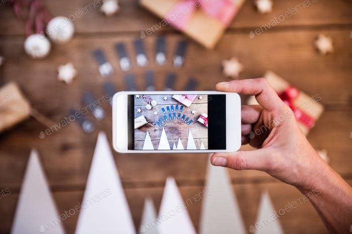 Ein Hand-Smartphone mit Weihnachtskomposition.