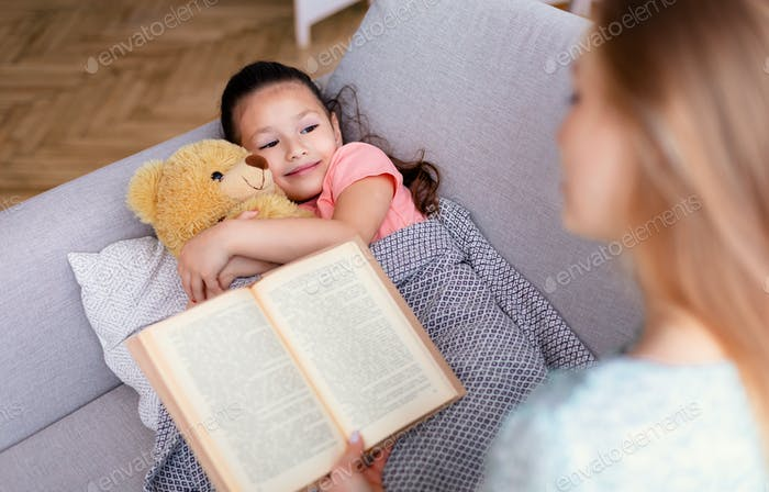 Mother Reading Bedtime Story For Little Daughter At Home