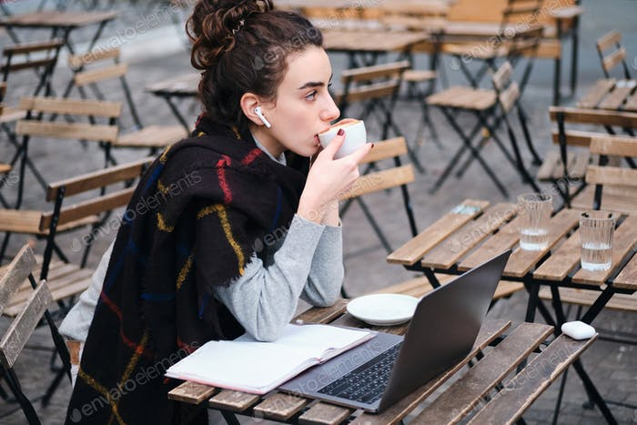 Attractive student girl with scarf drinking coffee studying with laptop in cafe on city street