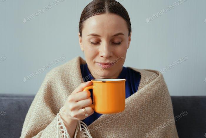 Positive Frau genießen eine Tasse Tee in einer Decke gewickelt