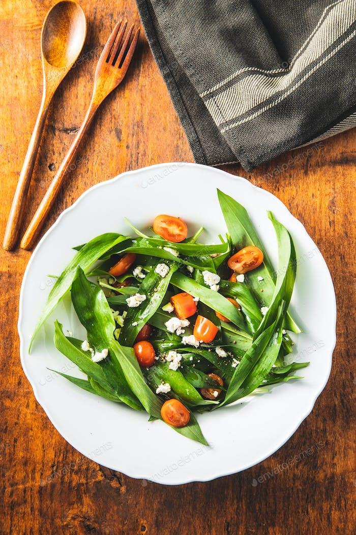 Frischer Salat mit Bärlauch, Tomaten und Feta-Käse auf Teller.