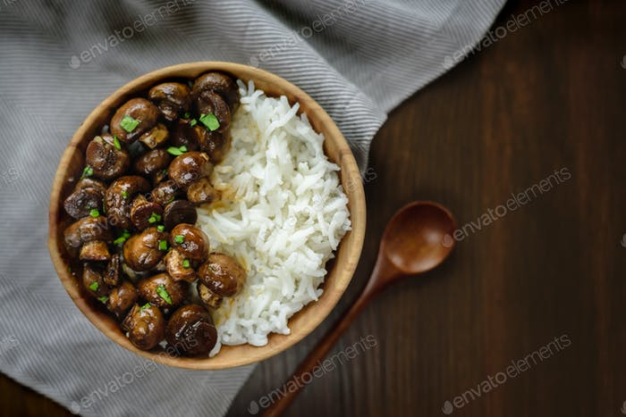 Sauteed white mushrooms with basmati rice in wooden bowl