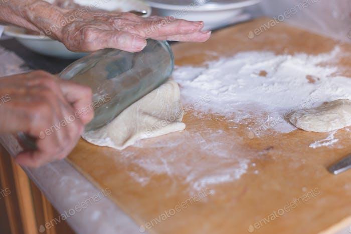 Hände der alten Frau auf abgeflachtem Teig