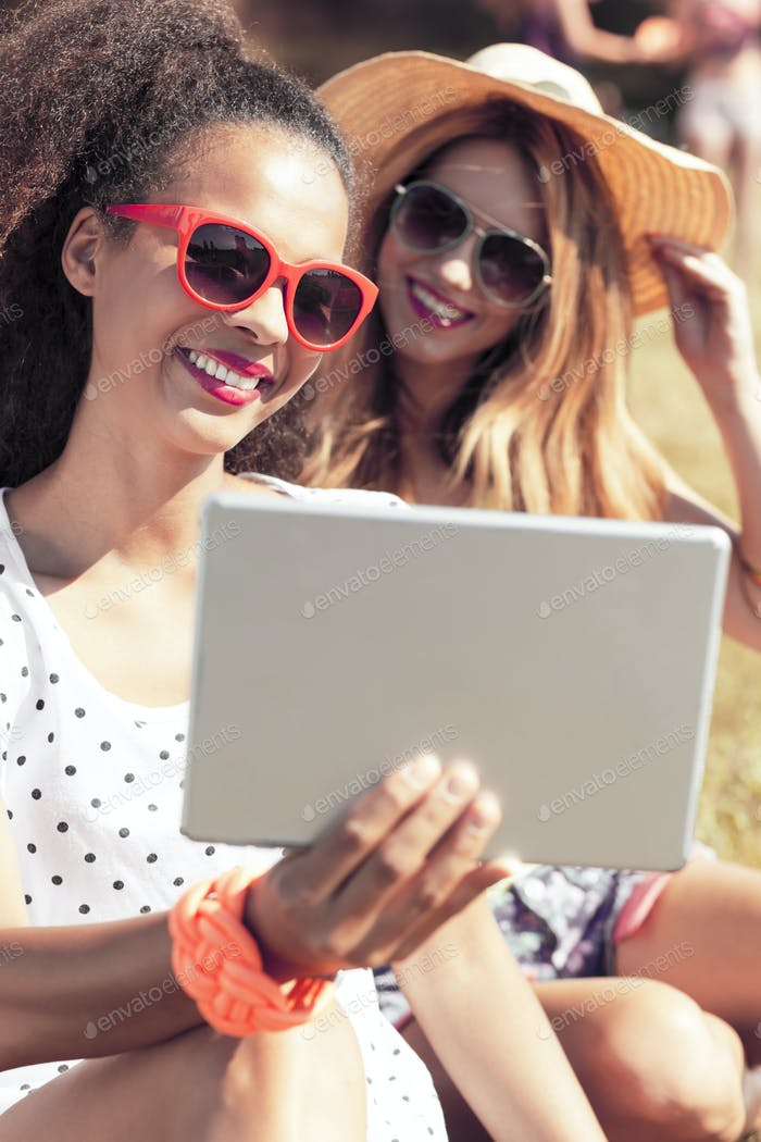 Women in sunglasses taking selfie with tablet