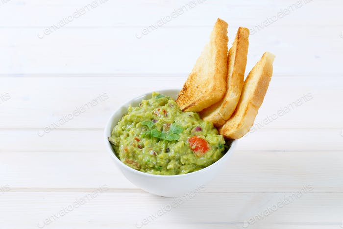 bowl of guacamole with toast