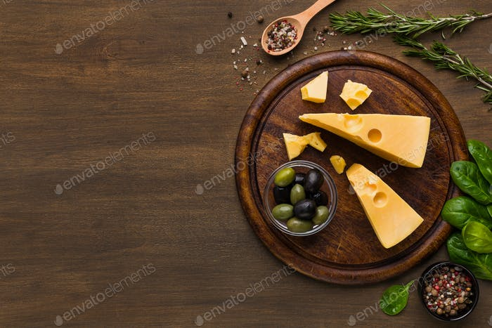 Cheese, olives and fresh herbs on wooden background