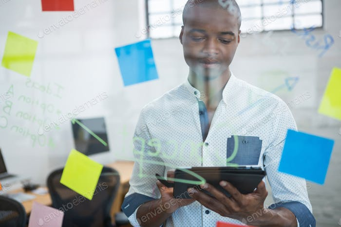 Businessman using digital tablet while writing on sticky note