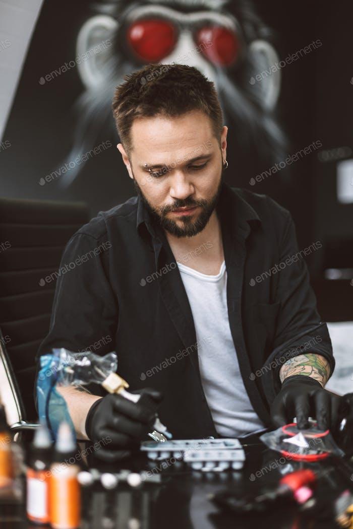 Professional tattooer in black gloves holding tattoo machine in
