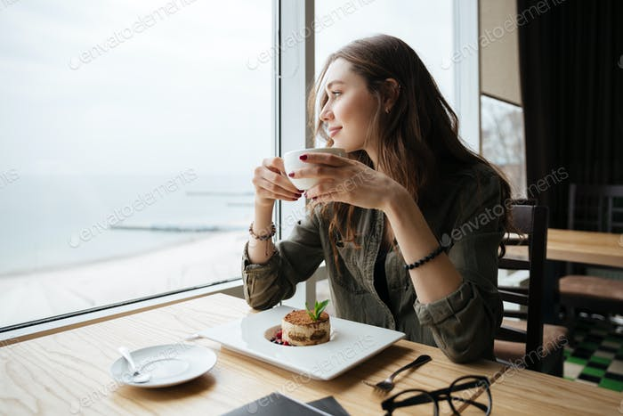Happy young beautiful lady sitting in cafe drinking coffee.