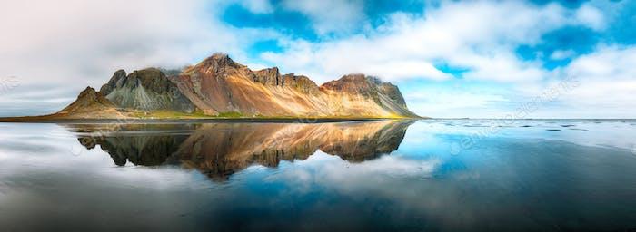 Herrlicher sonniger Tag und wunderschöne Reflexion des Vestrahorn-Gebirges am Stokksnes-Kap in Island.