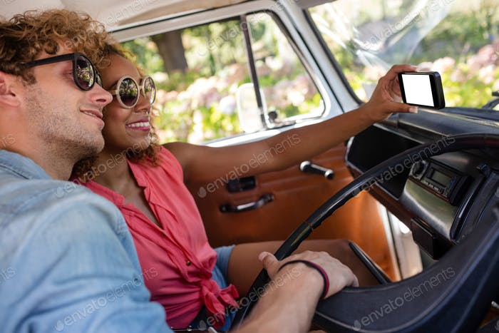 Couple taking a selfie while travelling in campervan