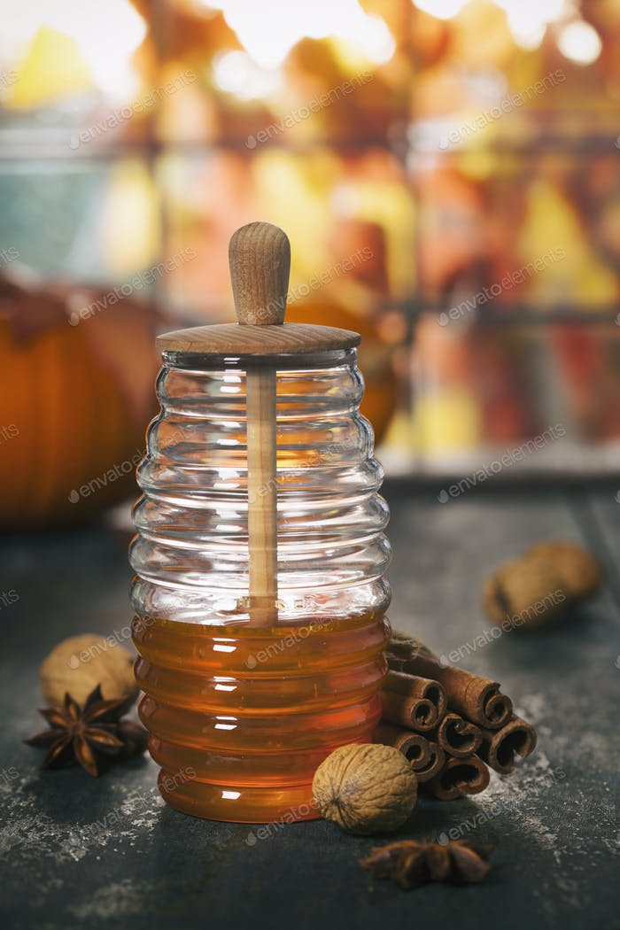 Autumn composition. Jar of Honey, pumpkins and spices on wooden window sill.