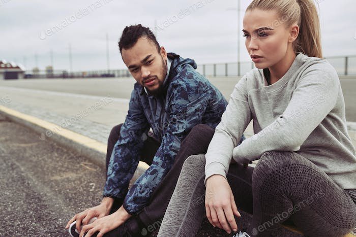 Tired couple resting on a road during an outdoor run