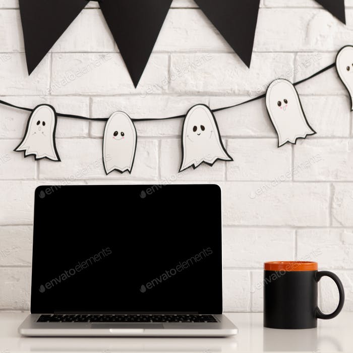 Desktop with laptop and scary holiday decorations