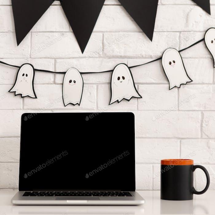 Desktop mit Laptop und gruseligen Urlaubsdekorationen