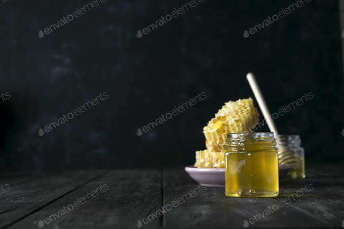 Honey jar with a wooden stick drains honey on an dark background , pure natural sweet goodness