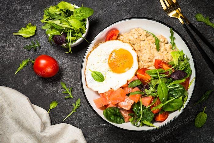 Herzhaftes Frühstück mit Haferflocken, Lachs und Salat.