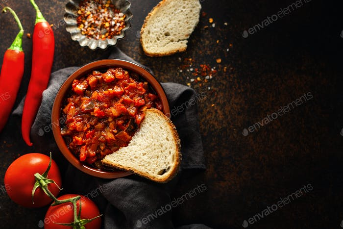 Fresh tasty tomato sauce on brown background