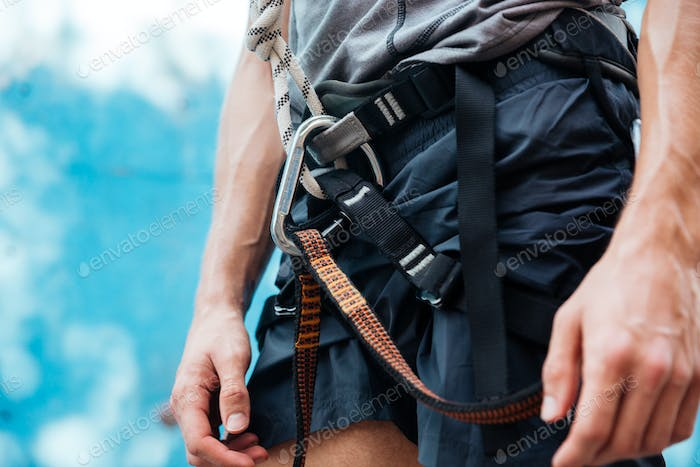 Close-up of climber wearing safety harness and climbing equipment