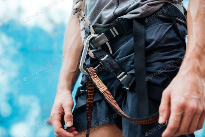 Nahaufnahme des Kletterers mit Sicherheitsgurt und Kletterausrüstung