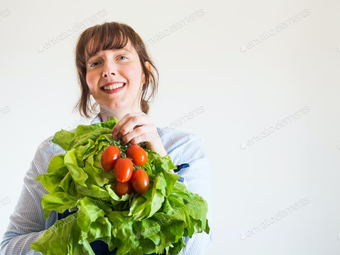 Woman in blue apron with fresh produce in hand