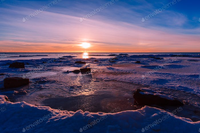 Winter nature landscape. Sunset over frozen sea.
