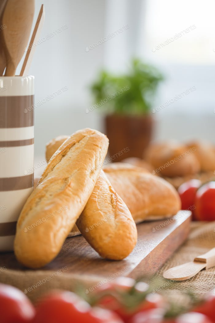 Close-up on baguette on wooden desk during breakfast with blurre