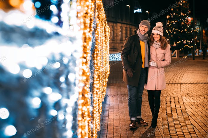 Happy couple walks on a street decorated for Christmas