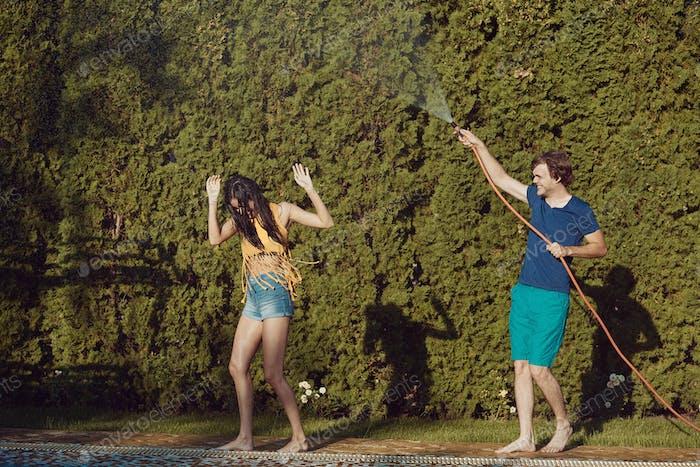 Couple having fun pour each other with garden hose