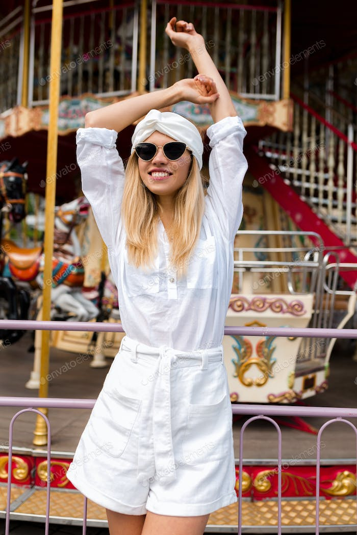Satisfied girl with blond hair wearing sunglasses and white outfit holding up hands and laughing