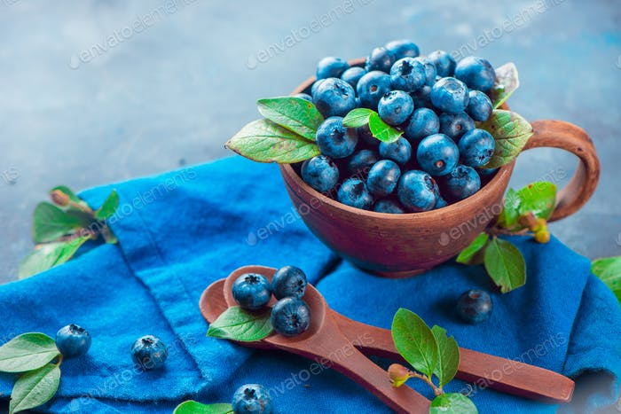 Handmade ceramic cup with blueberries. Ripe and sweet summer berries on a concrete background