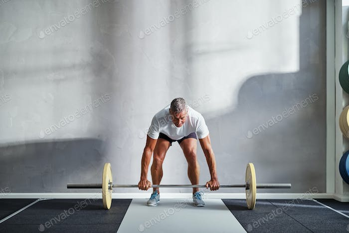 Fit mature man lifting weights alone in a gym
