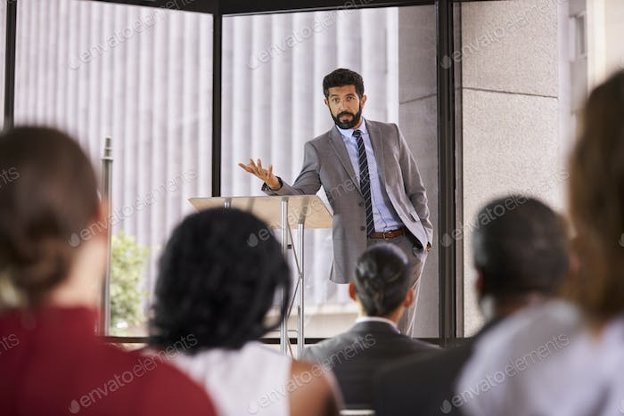 Thumbnail for Hispanic man presenting business seminar leaning on lectern