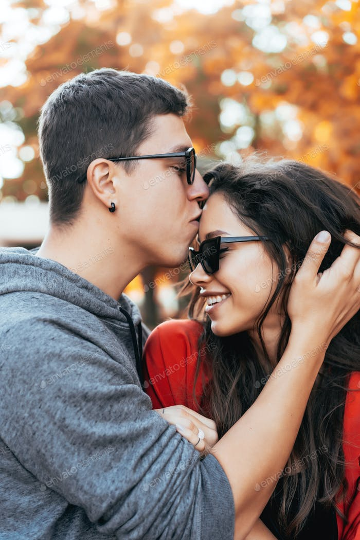 The guy gently kisses his girlfriend on the street