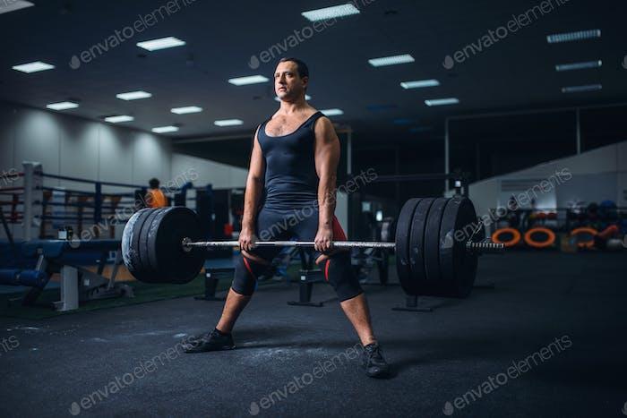 Male powerlifter preparing deadlift barbell in gym